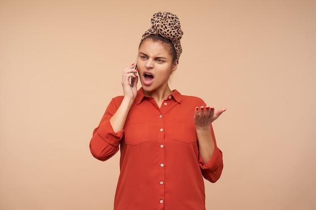 Wściekła młoda zielonooka brunetka kobieta z opaską podnosząca emocjonalnie rękę i krzycząca krzywo podczas nieprzyjemnej rozmowy telefonicznej, stojąca nad beżową ścianą