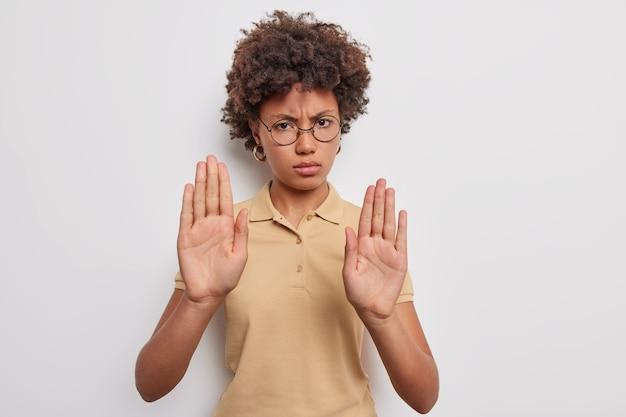 Wściekła niezadowolona afroamerykanka wyciąga dłonie i mówi, że nie pokazuje, gest zakazu, odmawia, coś nosi okrągłe okulary, casualową brązową koszulkę na białym tle nad szarą ścianą