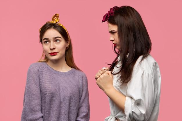 Wściekła, sfrustrowana młoda kobieta z gniewnym wyrazem twarzy jest wściekła na swoją przyjaciółkę, która ze zdumieniem patrzy w górę