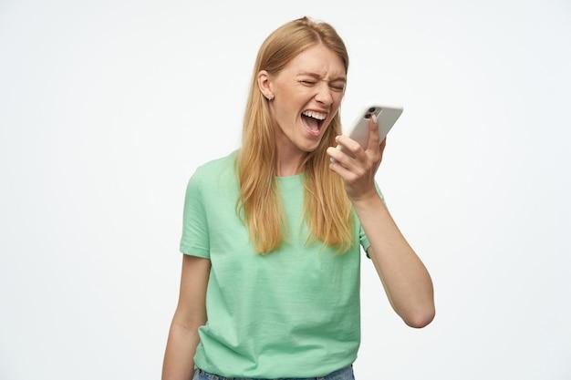 Wściekła, szalona kobieta z piegami w miętowej koszulce rozmawia przez telefon komórkowy i krzyczy na biało