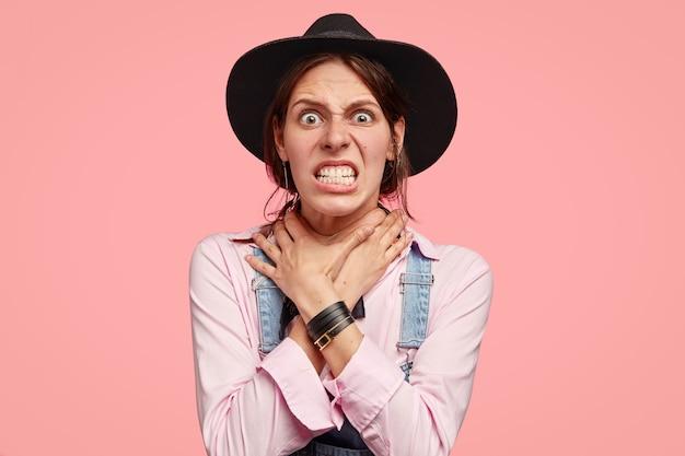 Wściekła szalona kobieta zaciska zęby, trzyma obie ręce na szyi, cierpi z powodu uduszenia