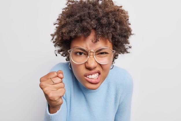 Wściekła zirytowana afroamerykanka zaciska pięści i zęby wyraża negatywne emocje, mając dość czegoś ubranego niedbale na białym tle nad białym tłem. koncepcja ludzi i reakcji