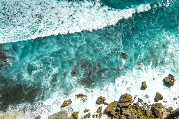 Wściekłe niebieskie fale oceanu biegną i rozbijają się o skały, widok z góry