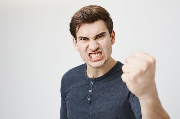 Wściekły agresywny facet krzywiący się i potrząsający pięścią grożący