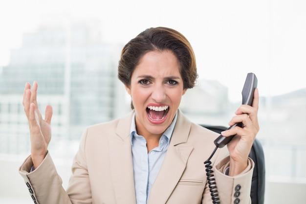 Wściekły bizneswoman patrzeje kamerę i trzyma telefon
