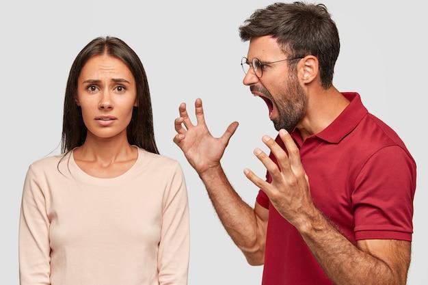 Wściekły brodaty facet krzyczy i gestykuluje ze złością, wrzeszczy na kobietę, kłóci się, pozuje