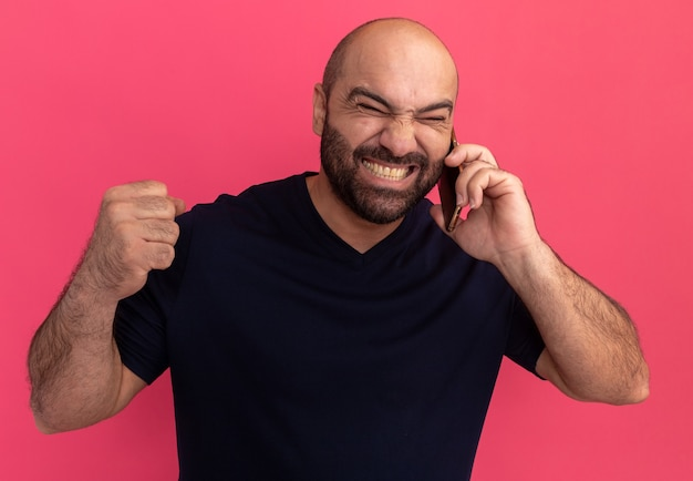 Wściekły brodaty mężczyzna w granatowej koszulce wyglądający na zirytowanego podczas rozmowy przez telefon komórkowy zaciskający pięść telefon stojący nad różową ścianą