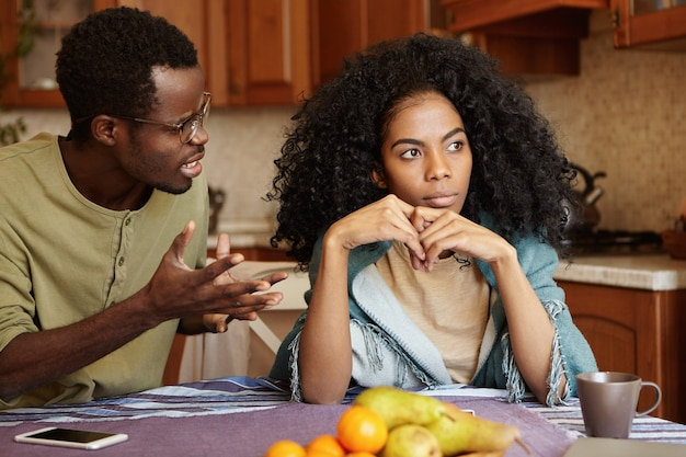 Wściekły czarny mężczyzna gestykulujący w rozpaczy lub złości, próbując usprawiedliwić swoją urażoną żonę, jakby mówił: czy możesz mnie po prostu wysłuchać? afrykańska para przeżywa ciężkie chwile w związkach
