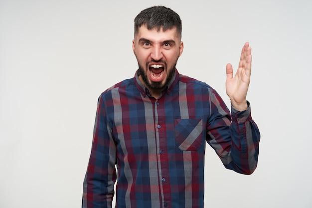 Wściekły dość młody, krótkowłosy, brodaty brunetka mężczyzna marszczy brwi i krzyczy gorąco z szeroko otwartymi ustami, pozuje na białej ścianie z podniesioną dłonią