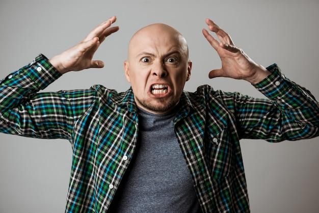 Wściekły gniew młody człowiek krzyczy na beżowej ścianie.