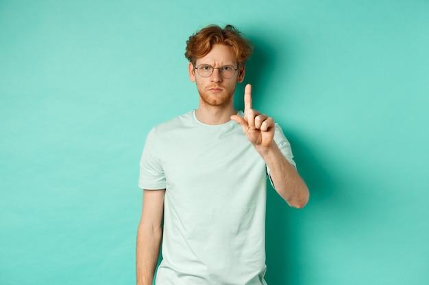 Wściekły i poważny młody człowiek z rudymi włosami, w okularach, pokazujący gest stop, mówiący nie, potrząsający palcem z dezaprobatą, stojący na miętowym tle.