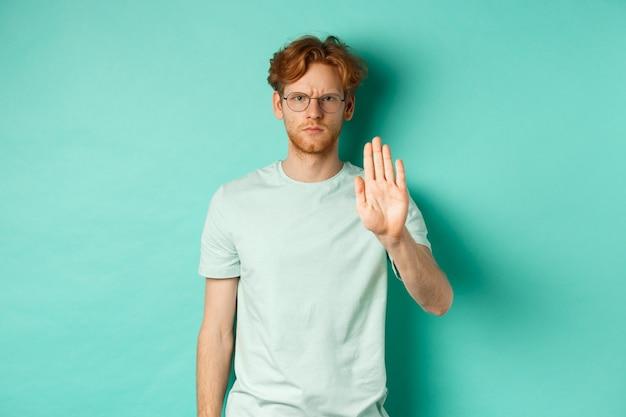 Wściekły i poważny młody człowiek z rudymi włosami, w okularach, pokazujący gest stop, odmawiający, dezaprobujący i zakazujący czegoś złego, stojący na turkusowym tle.