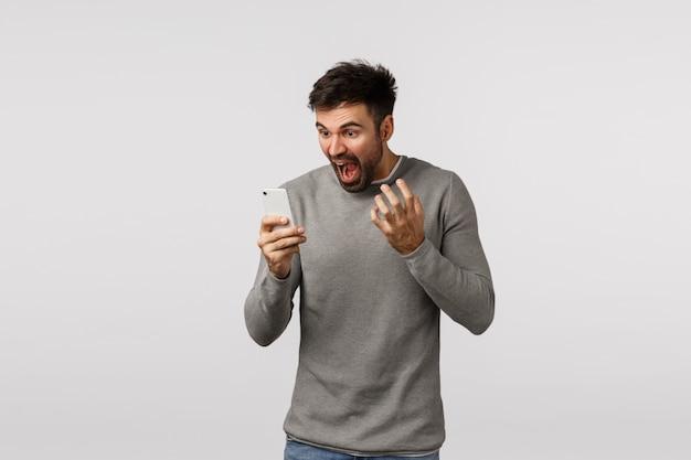 Wściekły i wściekły, wkurzony, napięty brodaty mężczyzna w szarym swetrze, trzymający smartfon, przeklinający, przeklinający na wyświetlaczu, krzyczący ekran telefonu i drżące ręce