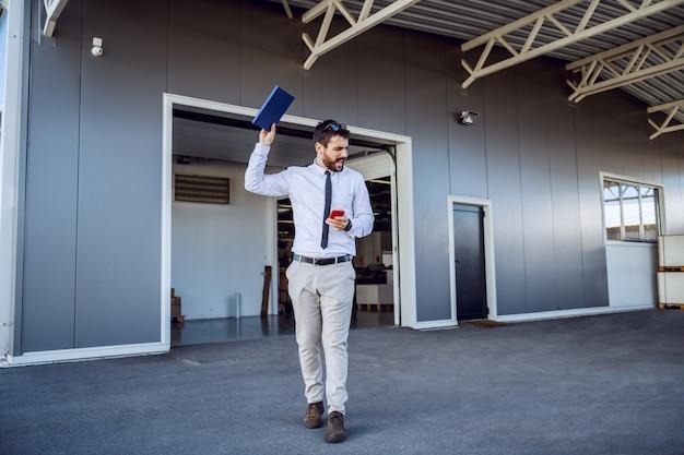 Wściekły kaukaski dyrektor idzie przed drukarnią, trzymając smartfon i notatnik i przeklinając.