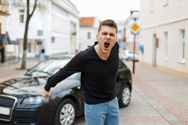Wściekły mężczyzna krzyczy w pobliżu samochodu w mieście. pojęcie gniewu