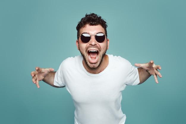 Wściekły mężczyzna z okularami przeciwsłonecznymi wrzeszczy i krzyczy na niebieską ścianę