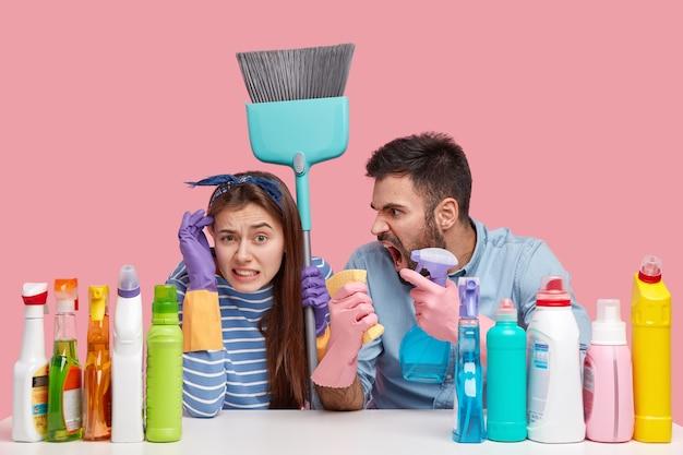 Wściekły mężczyzna ze sprzątaczki krzyczy na kobietę za złą robotę