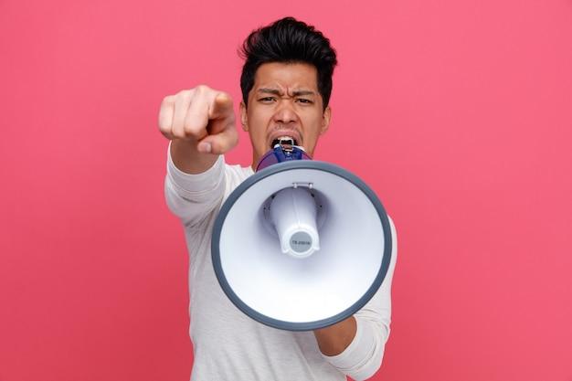 Wściekły młody człowiek patrząc i wskazując na aparat krzycząc w głośniku