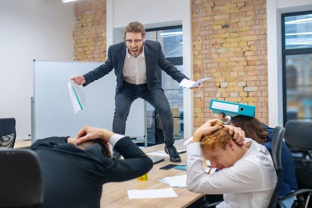 Wściekły, młody, dorosły mężczyzna w garniturze stojący na górze przy stole krzyczący i wystraszeni pracownicy chowający głowy