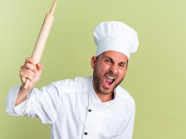 Wściekły młody kaukaski kucharz w mundurze szefa kuchni i czapce krzyczy trzymając wałek do ciasta