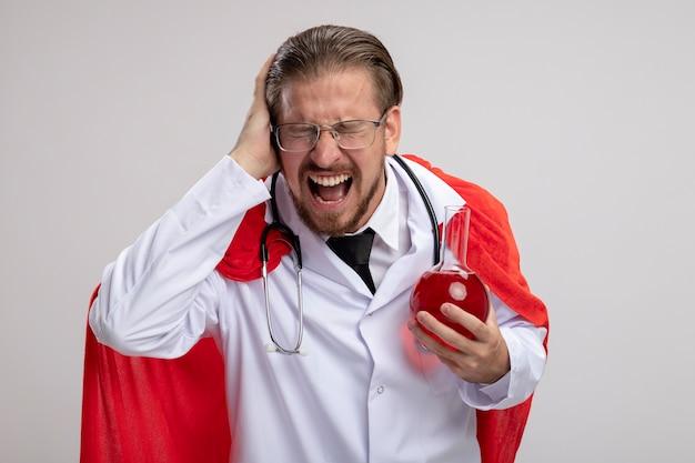 Wściekły młody superbohater w szlafroku medycznym ze stetoskopem i okularami trzyma szklaną butelkę chemii wypełnioną czerwonym płynem, kładąc rękę na głowie na białym tle