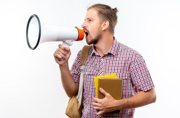 Wściekły młody uczeń facet noszący plecak trzymający książki mówi przez głośnik odizolowany na białej ścianie