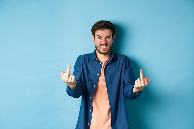 """Wściekły niegrzeczny facet pokazujący środkowy palec i mówiący """"pieprz się"""", przeklinający i wpatrzony wściekle w kamerę, stojący na niebieskim tle."""