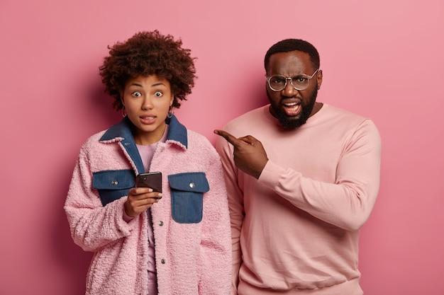 """Wściekły, niezadowolony mężczyzna w okularach wskazuje na afroamerykańską kobietę ze smartfonem, która wygląda na winną i mówi """"ups"""", uzależniona od nowoczesnych technologii. para etniczna pozuje razem w domu, będąc bardzo emocjonalną"""
