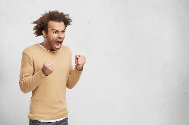 Wściekły ogłuszony mężczyzna krzyczy ze złości, trzyma pięści, zamierza się bronić