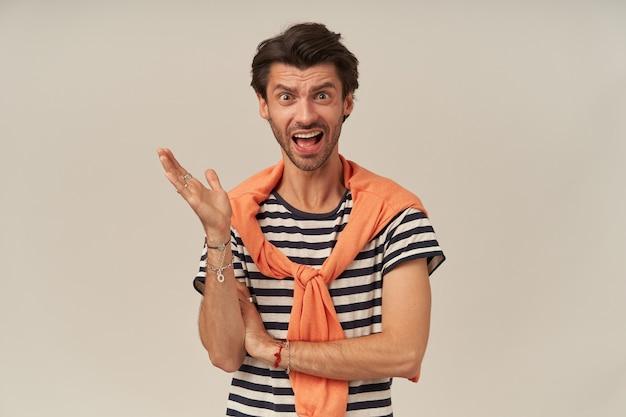 Wściekły, poirytowany młody człowiek z zarostem w pasiastej koszulce i swetrze na ramionach krzyczy i kłóci się