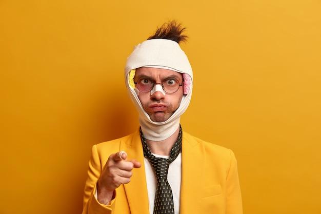 Wściekły ranny hospitalizowany mężczyzna wskazuje i obwinia kogoś o swój wypadek, ma wstrząs mózgu, owiniętą bandażowaną głowę, formalnie ubrany, odizolowany na żółtej ścianie, wymaga leczenia