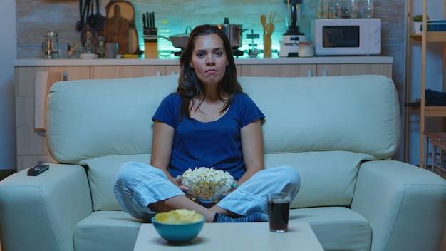 Wściekły rozczarowany fan sportu oglądający ulubioną drużynę i krzyczący w telewizji na zawodach piłki nożnej podekscytowana pani samotna w domu ciesząca się wieczorem siedząca na wygodnej kanapie ubrana w piżamę.