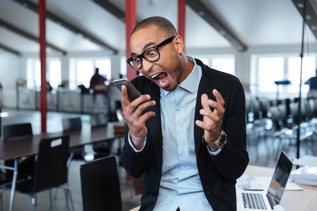 Wściekły szalony binessman rozmawiający krzycząc przez telefon w biurze