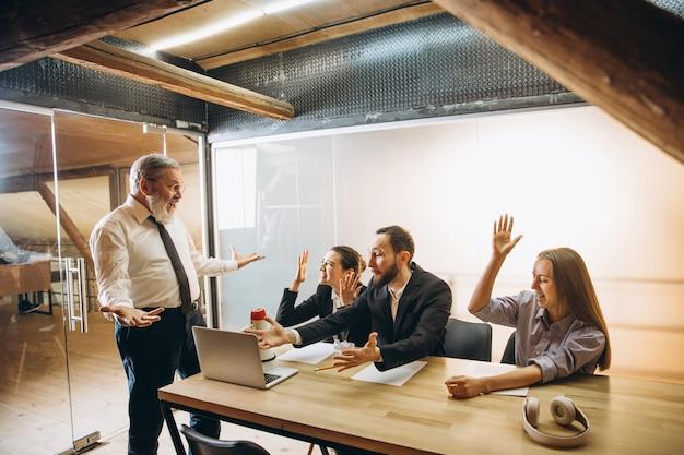 Wściekły szef z megafonem krzyczącym na pracowników w biurze, przestraszony i zirytowany koledzy słuchający przy stole zestresowani. zabawne spotkanie, biznes, koncepcja biura. krzyczeć szalony.