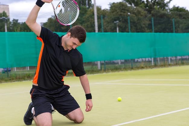 Wściekły tenisista w stroju sportowym złamie rakietę siedząc na kolanach z powodu przegranej w meczu tenisowym