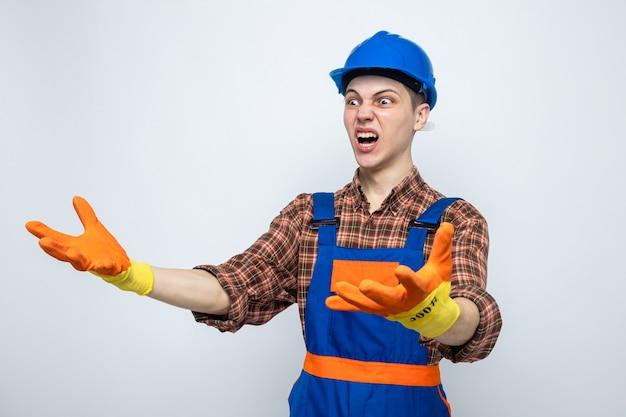 Wściekły, trzymający się za ręce młody budowniczy mężczyzna ubrany w mundur z rękawiczkami