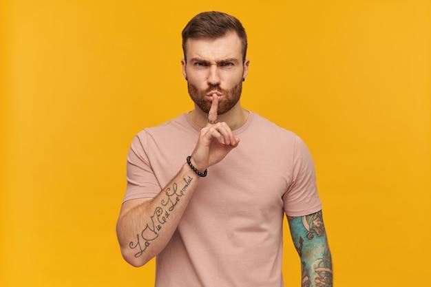 Wściekły, zirytowany młody mężczyzna w różowej koszulce z brodą i tatuażem na dłoni wygląda na zirytowanego i pokazuje gest ciszy palcem na żółtej ścianie patrząc na przód