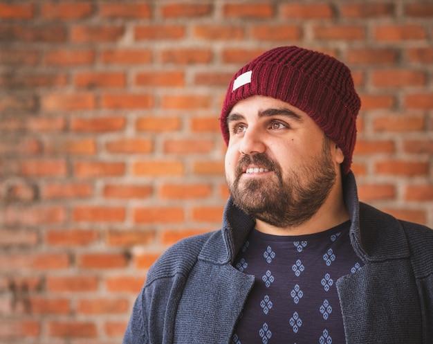 Wsiadł facet w wełnianej czapce i swetrze, uśmiechając się na ścianie z cegły