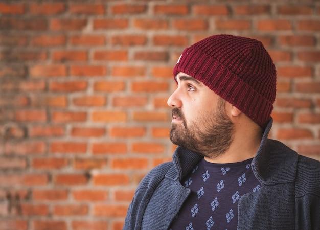 Wsiadł facet w wełnianym kapeluszu i swetrze, patrząc na bok na ścianie z cegły