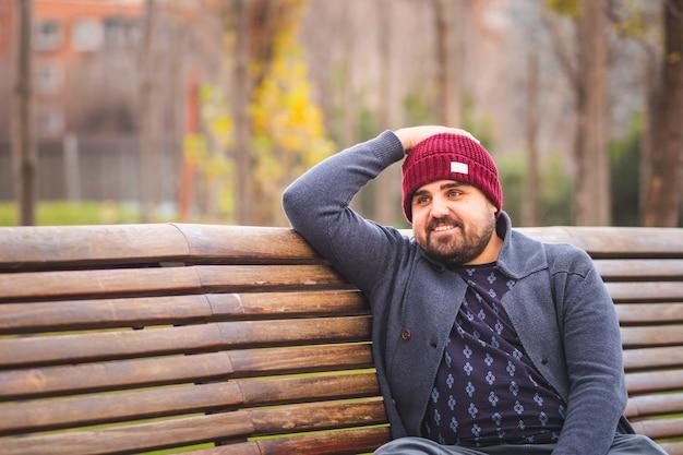 Wsiadł facet w wełnianym kapeluszu i swetrze, uśmiechając się i siedząc na ławce w parku