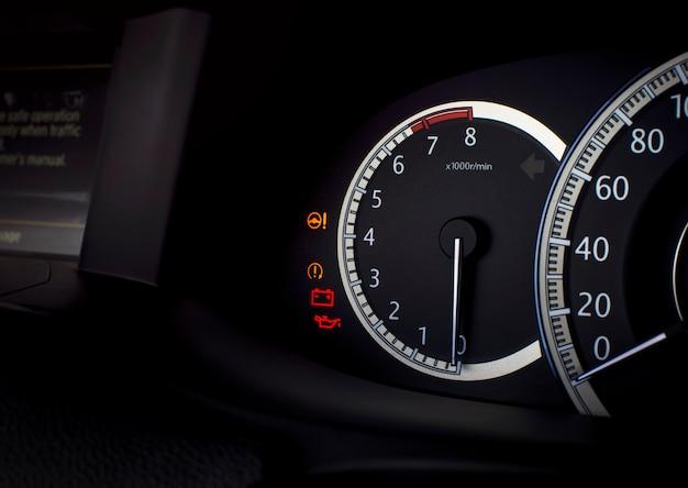 Wskaźnik prędkości obrotowej i lampka ostrzegawcza, takie jak elektryczny układ kierowniczy, akumulator, smar oleju silnikowego na desce rozdzielczej przebiegu w luksusowym samochodzie, koncepcja części samochodowej.