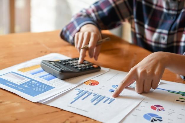 Wskaźnik strony na wykresie i innej ręce trzymać pióro i naciska kalkulator.