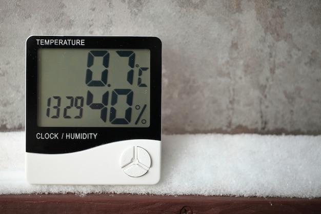 Wskaźnik wilgotności jest wskazywany na higrometrze zainstalowanym na śniegu. zdjęcie elektronicznego urządzenia do badania temperatury i wilgotności powietrza