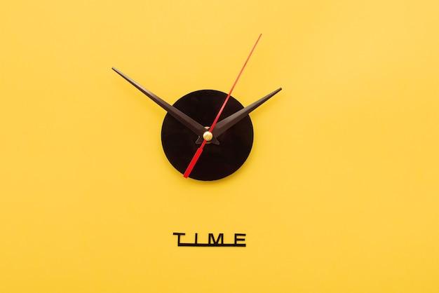 Wskazówki zegara na żółtym tle. koncepcja minimalnego czasu