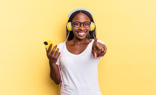 Wskazując na aparat z zadowolonym, pewnym siebie, przyjaznym uśmiechem, wybierając ciebie i słuchając muzyki
