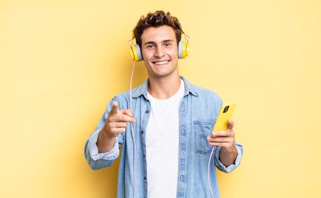 Wskazując na aparat z zadowolonym, pewnym siebie, przyjaznym uśmiechem, wybierając ciebie. koncepcja słuchawek i smartfona