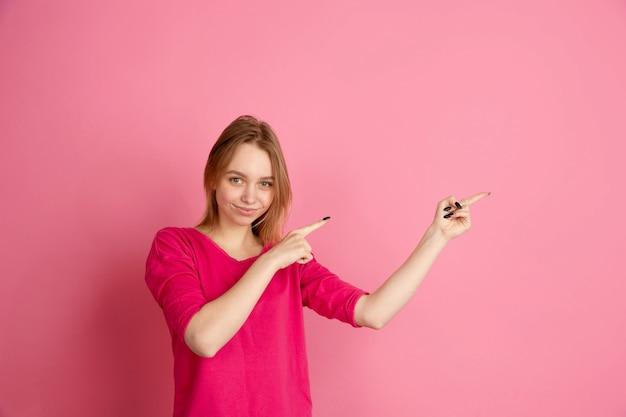Wskazując na bok. kaukaski portret młodej kobiety na białym tle na różowej ścianie, monochromatyczne. piękna modelka. pojęcie ludzkich emocji, wyraz twarzy, sprzedaż, reklama, modne.