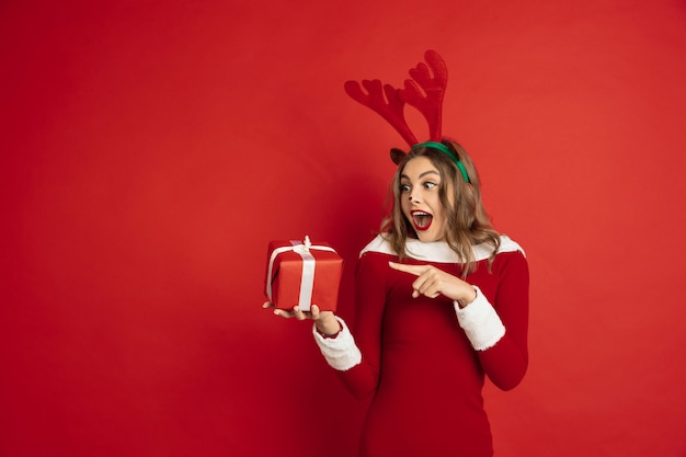 Wskazując prezentem. koncepcja bożego narodzenia, nowy rok 2021, zimowy nastrój, święta. . piękna kaukaska kobieta z długimi włosami jak renifer świętego mikołaja łapiący pudełko.