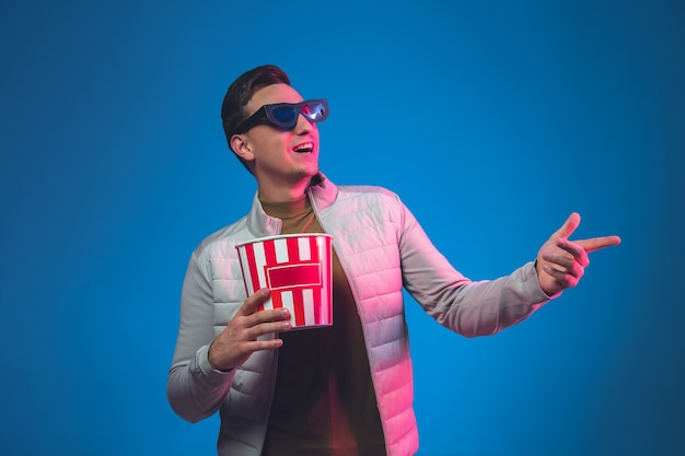 Wskazując w okularach 3d i popcornem. portret mężczyzny rasy kaukaskiej na białym tle. piękny męski model.