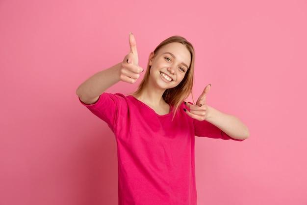 Wskazując, wybierając. kaukaski portret młodej kobiety na białym tle na różowej ścianie, monochromatyczne. piękna modelka. pojęcie ludzkich emocji, wyraz twarzy,